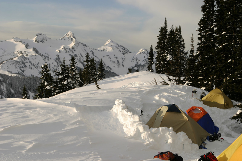 A group of tents high up on the side of Mt. Rainier is outlined against mountains of the Cascade range. This campsite was for an expedition of Boy Scouts.