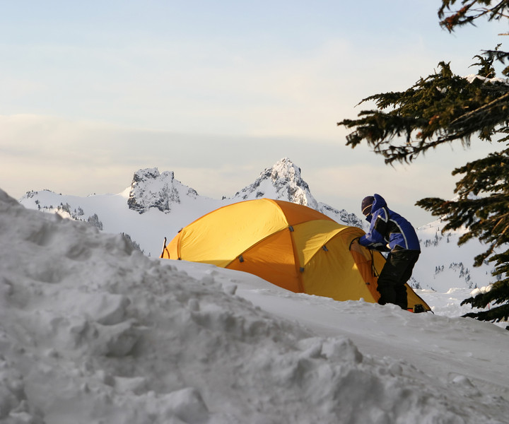 A boy getting out of his tent in the morning while on an expedition to Mt. Rainier in the winter.