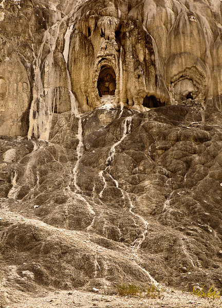 A rock formation resembling a ghostly face with mouth wide open and a river of tears. This image can be seen in Mound Terrace of Mammoth Hot Springs in Yellowstone National Park.
