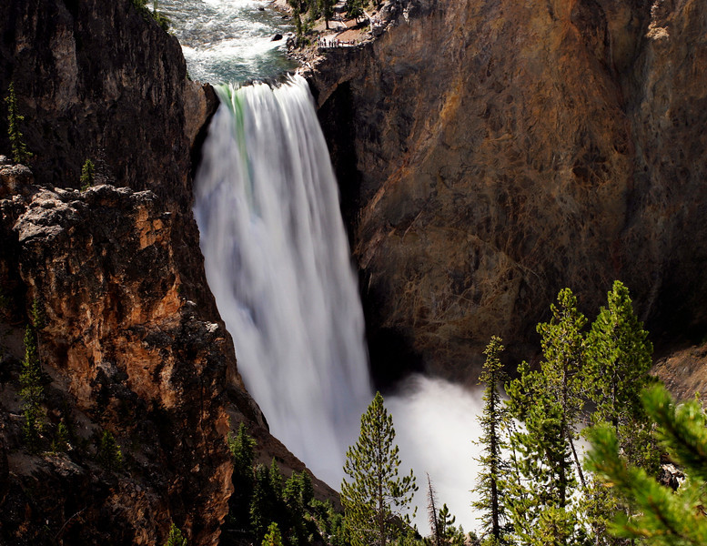 A timed exposure of the waterfall on the Lower Yellowstone River shows patterns of light in the water and mist. The viewpoint over the falls is visible.
