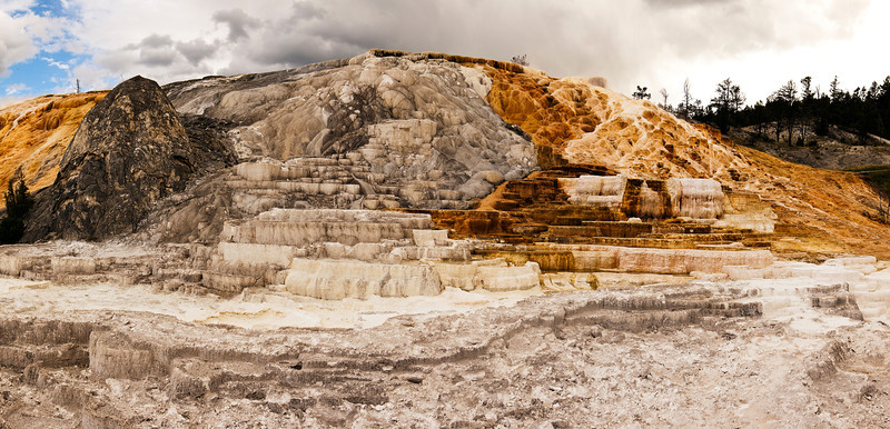 A view of one of the main features at Mammoth Hot Springs. The stone (travertine marble) is formed from the minerals in the water from the hot springs that have built up over years into a structure appearing like layers of a wedding cake.