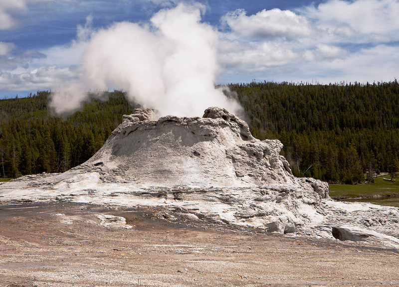Castle Geyser is one of the larger volcanic geysers in Yellowstone National Park. With a large cone formed after years of eruptions, this viewpoint shows steam rising from the top vent.