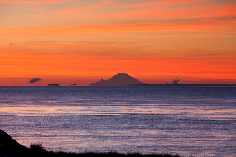 The bright orange colors of dawn illuminate a view of Mt. Rainier from San Juan Island over the waters of Puget Sound as viewed from over 120 miles away.