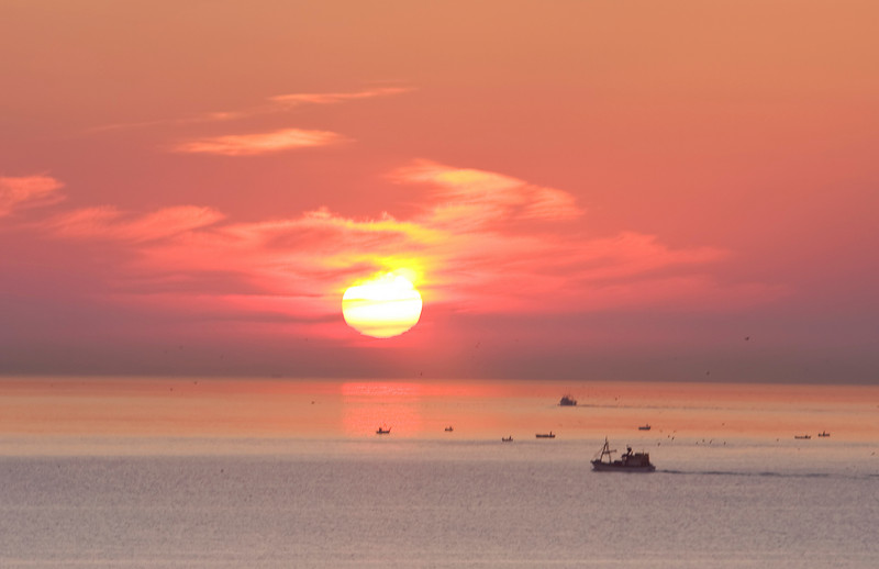 Morning sunrise with a deep red sun and color over the Costa del Sol with a fleet of small fishing boats in the foreground.