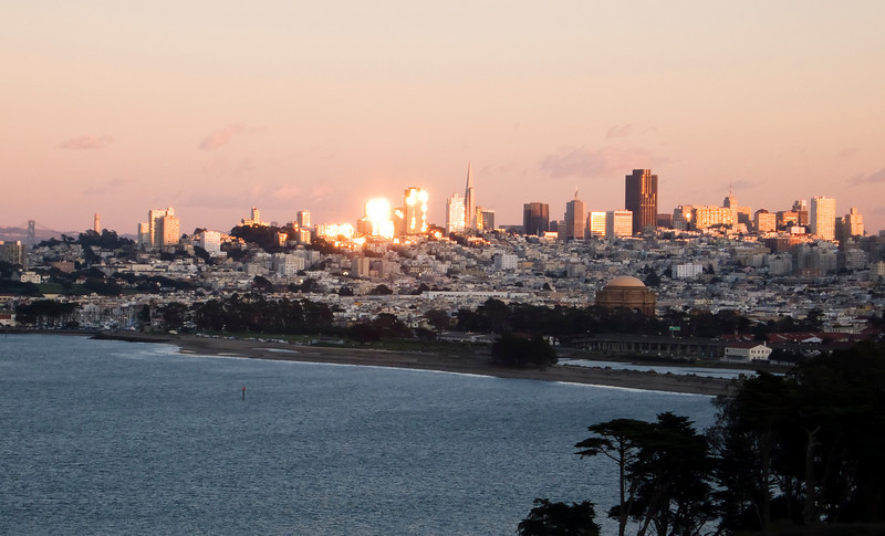 Sunset over San Francisco from the Golden Gate Bridge. This view looks over the Marina district, the Palace of Fine Arts, and Nob Hill. The highlights on the skyscrapers on the skyline are the reflection of the sun on windows.