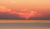 Morning sunrise with a deep red sun over the Costa del Sol with a fleet of small fishing boats in the foreground. The sun is not entirely up over the horizon and so only a small portion is visible.