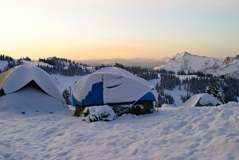 A small group of tents located together on Mount Rainier. After a snowstorm adventure over the previous night, an early morning sunrise greeted our group on Mt. Rainier.