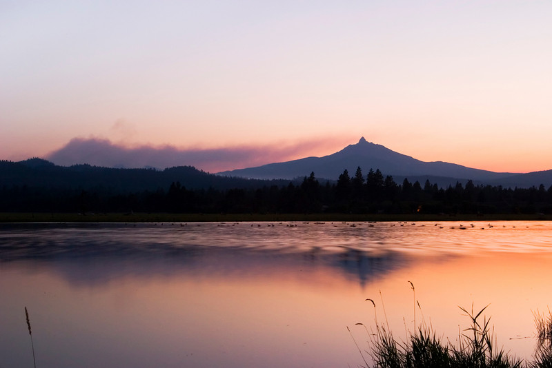 A fiery red sunset that is the result of smoke from the Lake George forest fire that burned in Central Oregon in the summer of 2006. The smoke particles in the air made the sky really red. The mountain on the horizon is Mt. Washington in the Oregon Cascades.