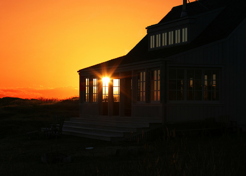 A glimpse of the sun that is shining through a window in a vacation house. The golden colors of sunset together with the halo and rays of light from the sun provide a tranquil scene.
