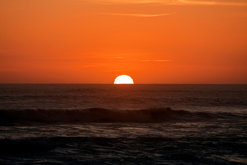 The sun slipping over the Atlantic Ocean at sunset near the Cape of Good Hope in South Africa. The circle of the sun is distorted by the air and clouds at the horizon.
