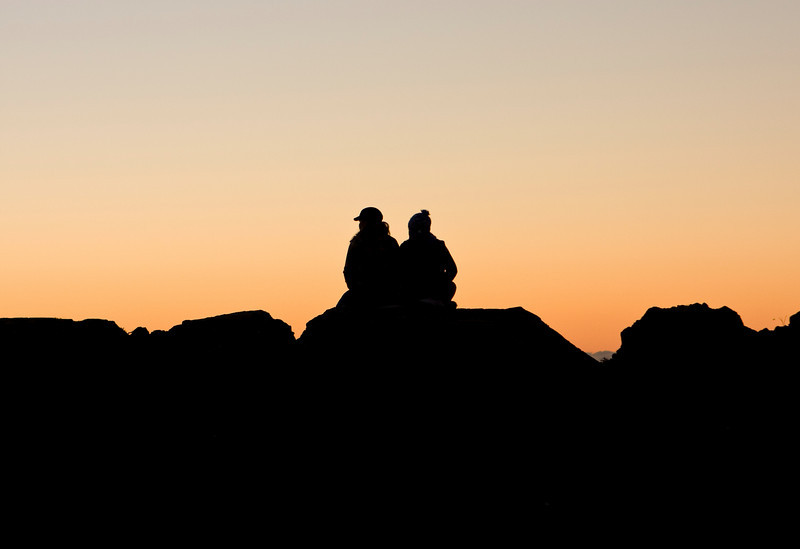 A couple, sitting on a pile of rocks at the beach, are watching a colorful sunset.