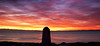 A colorful, dramatic sunset from San Juan island looking west towards the Straits of Juan de Fuca and Vancouver Island. The concrete obelisk in the foreground is a US geological marker.