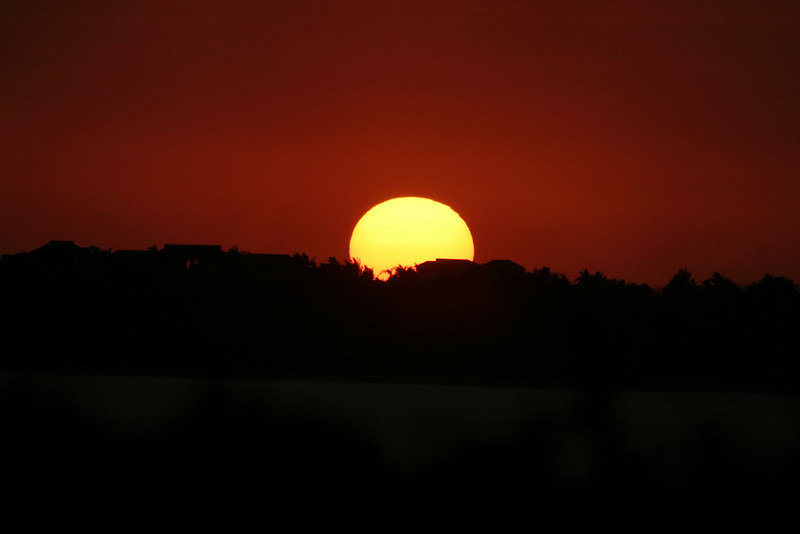 The sun going down over the horizon with deep red and orange colors. The sun is distorted by the dust in the air and the heat rising from the earth in the foreground.