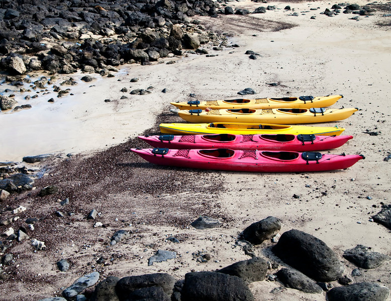Five kayaks are waiting on the beach at Puerto Baquerizo Moreno on San Cristobal Island in the Galapagos for the start of an ecological adventure.