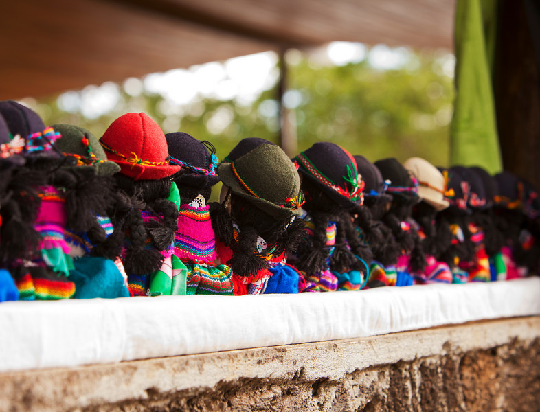 A view of the back of a row of traditional Ecuadorian dolls with the typical native hats from outside a handicrafts store on the Galapgos Islands.