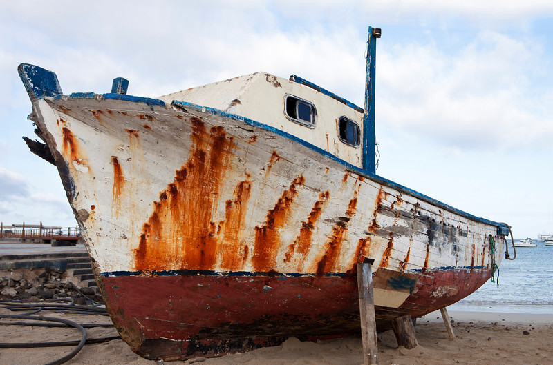 An old boat, weathered by the elements, is pulled up on the beach in the harbor of Puerto Baquerizo Moreno on the Galapagos Islands.