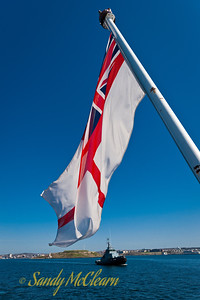 The White Ensign flies from the ensign staff at SACKVILLE's stern with Glenside in the background. The White Ensign was the RCN's ensign until 1965, when it was replaced with the Maple Leaf, Canada's national flag.