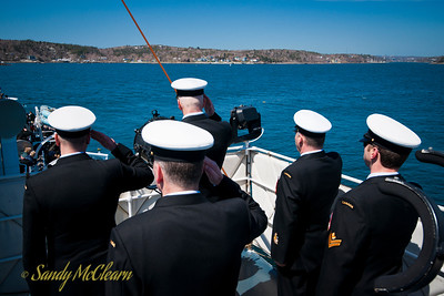 Senior enlisted personnel on the bridge salute as each sailor is buried at sea.