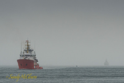 HMCS ST. JOHN'S, barely visible in the fog, stalks CCGS Earl Grey into Halifax Harbour.