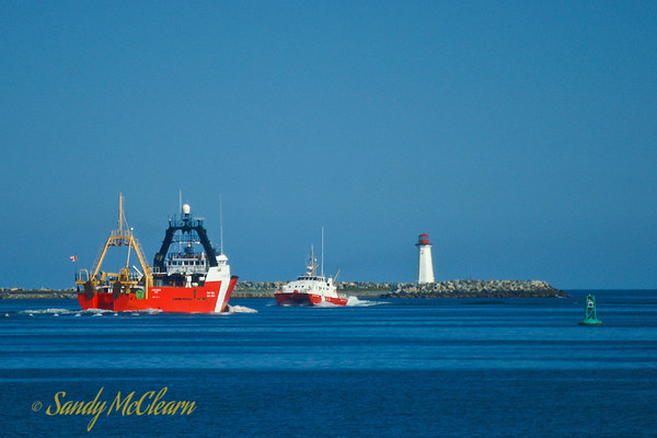 CCGS Alfred Needler passes CCGS Frederick G. Creed with the McNab's Island lighthouse in the background.