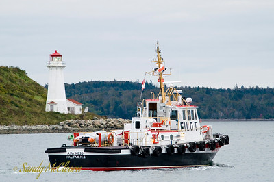 A pilot boat in Halifax Harbour passes the lighthouse on George's Island.
