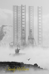 A passenger ferry passes in front of a jack-up oil rig amongst sea smoke in Halifax Harbour.