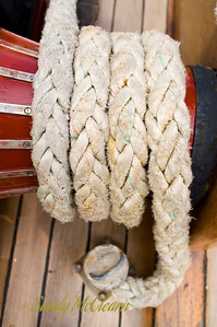 Rope coiled on a winch at the bow of a sailboat.