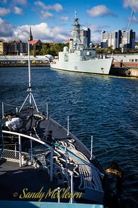 HMCS IROQUOIS (DDH 282) lies in HMC Dockyard as SACKVILLE approaches.