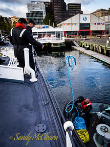 A member of MERRICKVILLE's crew tosses a line up to HMCS SACKVILLE.
