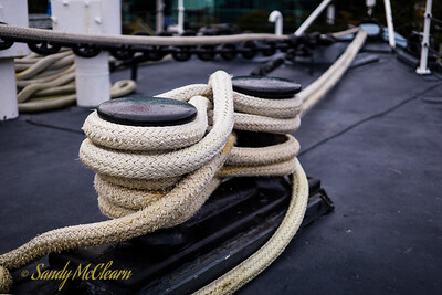 Rope coils around a bollard before heading to the bullnose at SACKVILLE's bow.