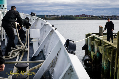 Sailors on the quarterdeck recover a stern line already cast off from the wharf.