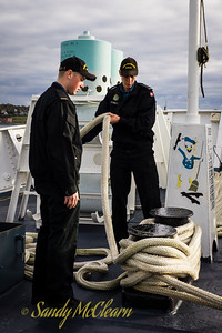 Sailors removing a rope from a bollard on the quarterdeck.