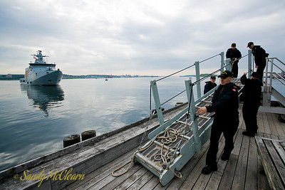 A work crew from HMCS ATHABASKAN sets up the brow (gangway) as HDMS EJNAR MIKKELSEN comes alongside Cable Wharf.