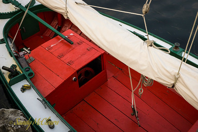 """The flywheel of a single cylinder """"one-lunger"""" peaks out from its housing in a small traditional boat."""