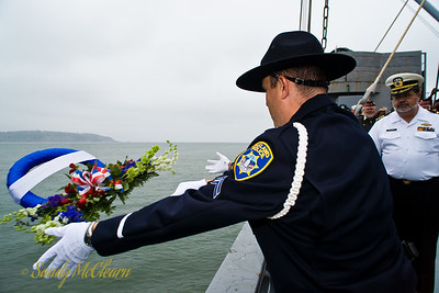 Two Oakland Police officers form an Honour Guard to throw a wreath in the bay in memory of four fallen officers.