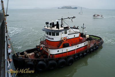 A tug stands ready to pull S.S. Jeremiah O'Brien out from her wharf with Alcatraz in the background.