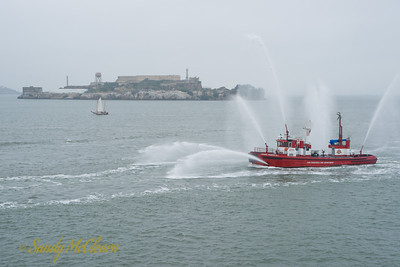 The San Francisco fire boat escorts the S.S. Jeremiah O'Brien around the Bay during the Memorial Weekend cruise. The two monitors firing water on either side of the bow are for putting out fires under wharves. Alcatraz is in the background.