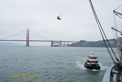 A view from the S.S. Jeremiah O'Brien on the seaward side of the Golden Gate Bridge, with a tug and a US Coast Guard helicopter also in the view.