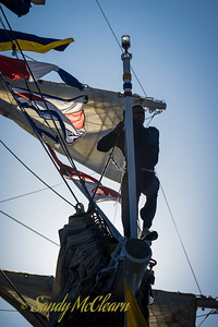 One of A.R.C. Gloria's sailors stands on the bowsprit, ready to raise the ship's jack.