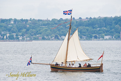 One of many generic 18th century replica longboats sails along the waterfront. These boats were used in a symbolic re-enactment of the founding of the Royal Navy Dockyard in Halifax.
