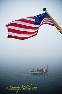A replica Royal Navy longboat rows under the Stars and Stripes hanging from the transom of USCGB Eagle.