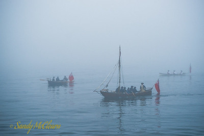 Several longboats in the fog.