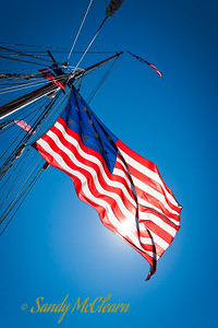 The Stars and Stripes, backlit by the sun,  flies from Pride of Baltimore II.
