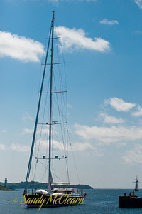 A modern sailboat approaches her berth on the waterfront.