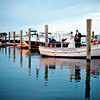 Bride and groom taking wedding photos on the boat launch at Nauticus Marina on Cape Cod. (By Bello Photography)