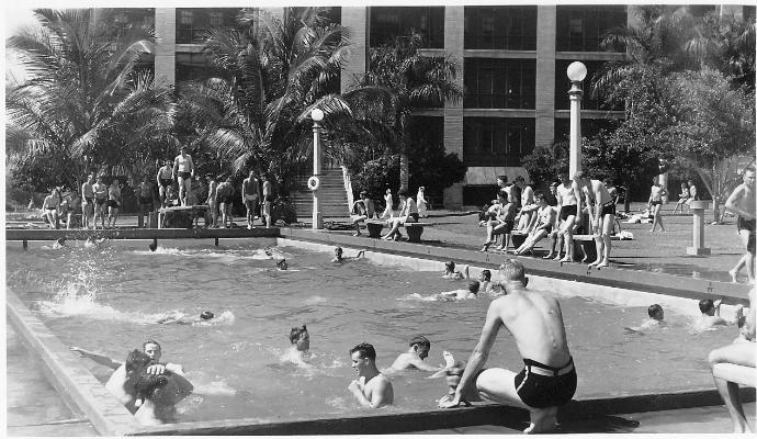 "Submarine crews and other enlisted men assigned to Pacific Fleet Headquarters, Pearl Harbor, Hawaii, enjoy the swimming pool outside their barracks.  Summer 1941.  <br /> <br /> During my enlistment (1956 to 1958) CINCPAC/CINCPACFLT personnel were housed in the right wing of the barracks on the third deck. We were in the area of the fourth opening (not shown) of the Lenai facing the long view of the swimming pool.<br /> <br />          Above photo illustrates Radioman, Chapter 7 (""The Submarine Base""), page 49<br />                                        Source of Photo:  Ray Daves Collection"
