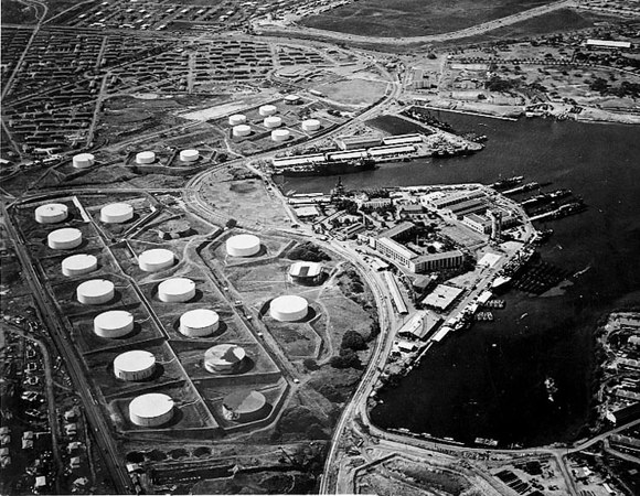 This is an aerial view looking back over the Sub Base at Pearl Harbor HI prior to December 7, 1941 attack.  Note Sub Base Barracks 654 Paquet Hall, (U shape building) with swimming pool on front lawn and Sub Base Escape Training Tower located in middle right of this photo. Oil Tank Farm located behind the barracks.<br /> <br /> Original location of CINCPAC/CINCPACFLT Headquarters in 1941 was located near the Training Tower of the Sub Base.  Headquarters were later moved to Makalapa Hill overlooking Pearl Harbor.<br /> <br /> Aerial view of the Submarine Base (right center) with the fuel farm at left, looking south on 13 October 1941. Among the 16 fuel tanks in the lower group and ten tanks in the upper group are two that have been painted to resemble buildings (topmost tank in upper group, and rightmost tank in lower group). Other tanks appear to be painted to look like terrain features. Alongside the wharf in right center are USS Niagara (PG-52) with seven or eight PT boats alongside (nearest to camera), and USS Holland (AS-3) with seven submarines alongside. About six more submarines are at the piers at the head of the Submarine Base peninsula.<br /> <br /> Official U.S. Navy Photograph, now in the collections of the National Archives.  October 13, 1941 Photo.