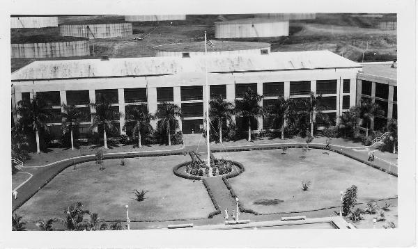 """The enlisted men's barracks (U shape building - 654 Paquet Hall) housed submarine crews and other sailors on duty at Pacific Fleet Headquarters, Pearl Harbor, Hawaii.  Summer 1941.<br /> <br /> During my enlistment (1956 to 1958) CINCPAC/CINCPACFLT personnel were housed in the right wing of the barracks on the third deck.  We were in the area of the fourth opening (not shown) of the Lenai facing the long view of the swimming pool.<br /> <br />           (Round objects behind the barracks are fuel storage tanks, also known as """"the tank farm."""")<br /> <br />         Above photo illustrates Radioman, Chapter 7 (""""The Submarine Base""""), pages 49 to 57<br />                                             Source of Photo:  Ray Daves Collection"""