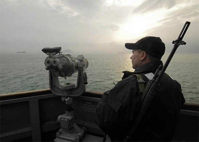 Gunner's Mate 2nd Class Michael West monitors surface contacts in Hong Kong Harbor from the bridge of the guided missile destroyer USS Shoup (DDG 86).