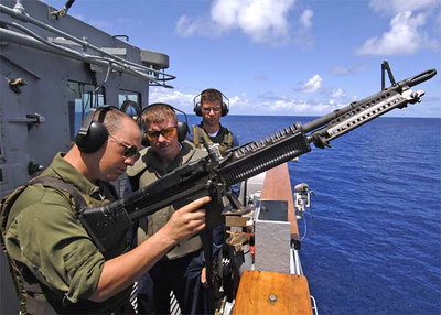 Seaman Thomas J. Tafoya, left, receives instruction on firing an M-60 machine gun from Chief Gunner's Mate Louis Johnson during a live fire exercise aboard the Ticonderoga-class guided missile cruiser USS Monterey (CG 61).